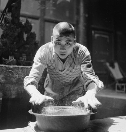CHINESE TEMPLE AT NORTH HOT SPRINGS. A TEMPLE BOY MOVES HIS HANDS OVER AN ANCIENT BRONZE BOWL TO MAKE IT SING AND THE WATER DANCE