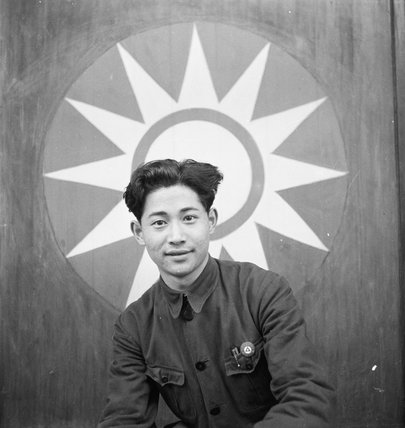 Portrait of a Chinese actor in front of the Kuo Min Tang National People's Party emblem at Chungking, Szechuan, China, 1944.  The actor belonged to a theatre troupe which specialised in entertaining Chinese troops