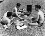 Three men on Brighton Beach with a record player: c. 1955