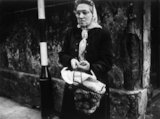 An elderly woman wearing a headscarf: 1961