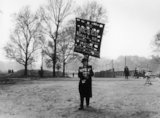 A man walking in a park holding a banner: 1961