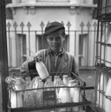 A boy in a school cap and overalls takes a milk bottle from a crate. c.1955