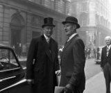 Three formally dressed men on a street flanked by high buildings. c.1955