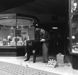 Two men selling mechanical toy dogs. c.1955