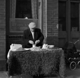 Man behind a seafood stall outside a pub. c.1955