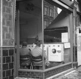 Two men sit in a launderette. c.1955
