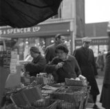 Two women buying groceries from a street stall. c.1955