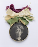 Glass-fronted medallion, containing portrait of Mrs Pankhurst and suspended from bunch of mauve, white and green ribbon.