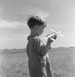 Boy holding model aeroplane at Fairlop: 1952