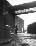 A Policeman stands beside a carriage in front of warehouse buildings. c 1934