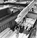 Discharging timber onto craft at the Surrey Docks: 1964