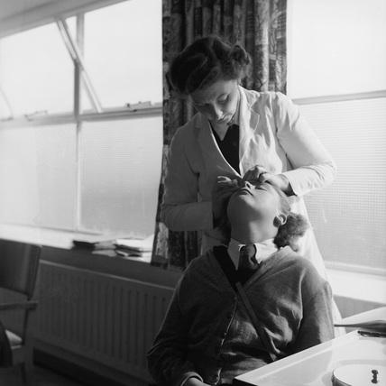 A nurse examining a schoolgirl's eye: 1958