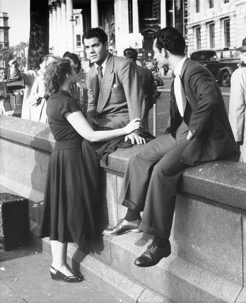 Friends sit on a wall in Trafalgar Square; c.1955