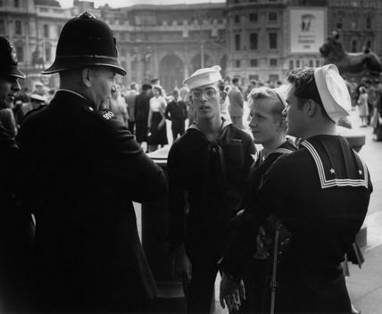 Policeman talking to three sailors in Trafalgar Square: c. 1950