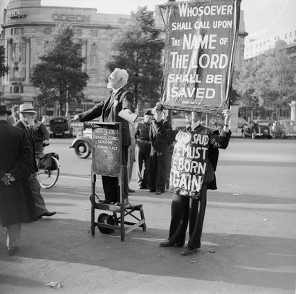 Two men from the Society for Evangelising London preaching to passers-by in the street: c. 1955