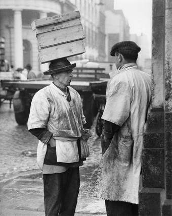 Two men in conversation outside Billingsgate Fish Market: 1958
