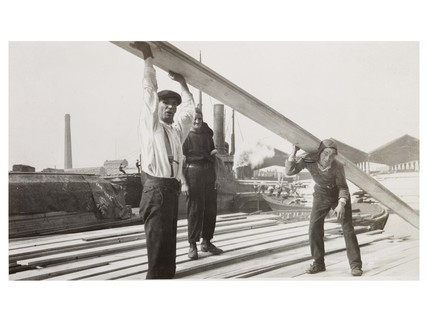 Men moving timber at Surrey Docks: c. 1930