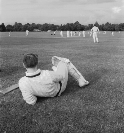 Cricketer watching a cricket match; c1965