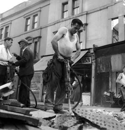 Men digging up the road; 1955