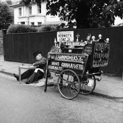 Tradesman with his street cart, recaning a chair; 1956