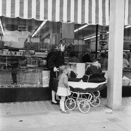 Woman standing with her children outside a supermarket in London; c 1959