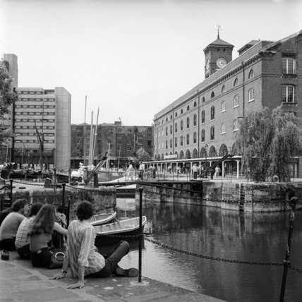 Young people sit on the quayside at St. Katharine's Dock; 1975- 1978