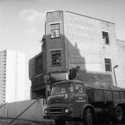 A man stands on a loaded lorry besides a partially demolised building in Kilburn; c.1972