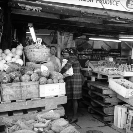 Woman buying  fruit and vegetables from a grocer;