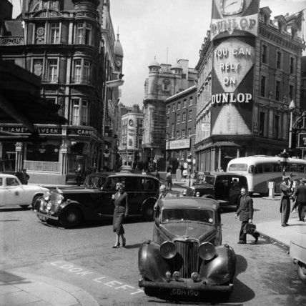 Traffic and passers-by in Soho; c 1965