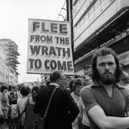 View of crowds near a banner reading 'Flee from the wrath to come'.