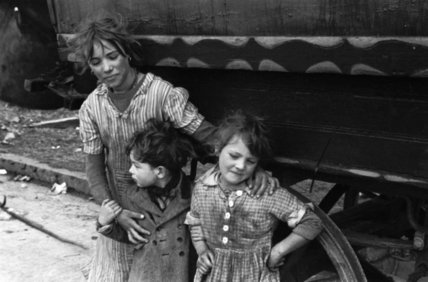 Group of gypsy children photographed alongside their caravan; 1953