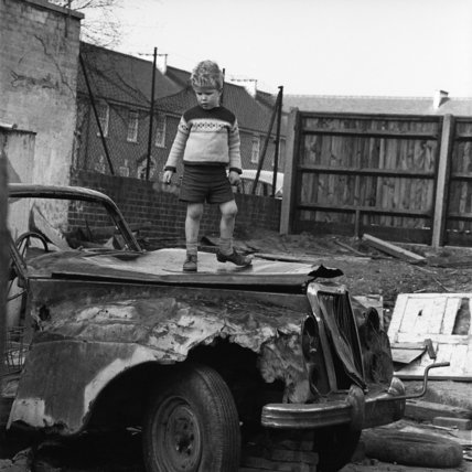 Child playing on an abandoned car in an adventure playground; c.1965