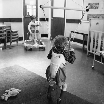 A young child in a baby bouncer walking frame; 1965