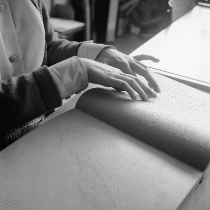 Woman's hands reading a braille book; 1965