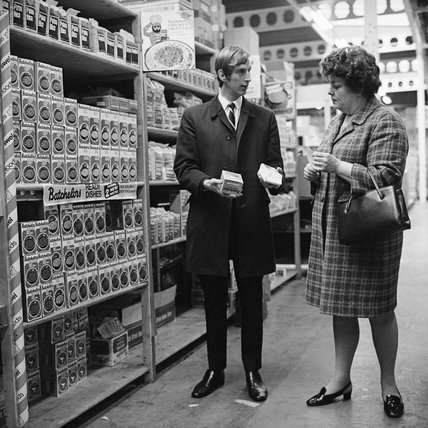 Woman shopper with a shop assistant in the soup aisle of a supermarket; c 1965