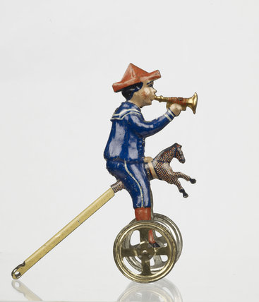 Tinplate toy figure of a boy astride a hobbyhorse; 1902