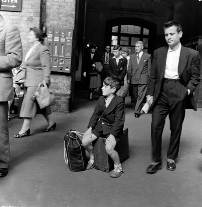 Boy sitting on his suitcase at Kings Cross Station; 1955