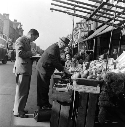 Inspector of Weights and Measures at a vegetable stall; 1955