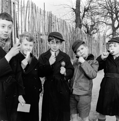 A group of boys eating ice creams and toffee apples in the playground; 1957