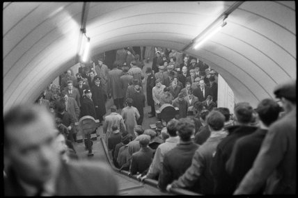 Commuters on an escalator; c.1960