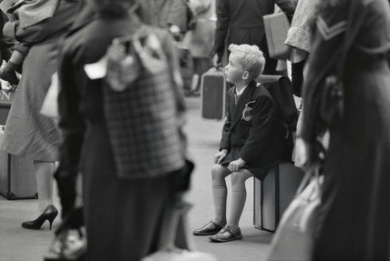 Young boy sitting on a railway station platform: c.1960