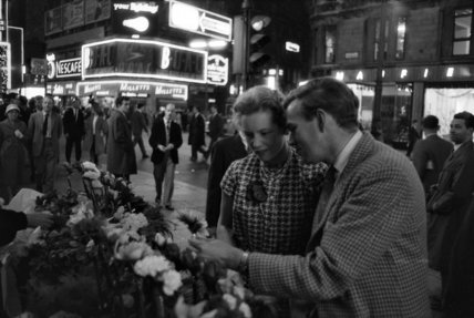 Man buying a woman a flower in the West End: 1960