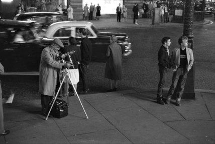 Photographer recording the nightlife; c.1960