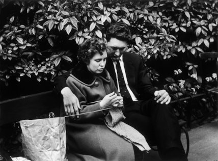 A couple sit on a bench in a park, c.1961