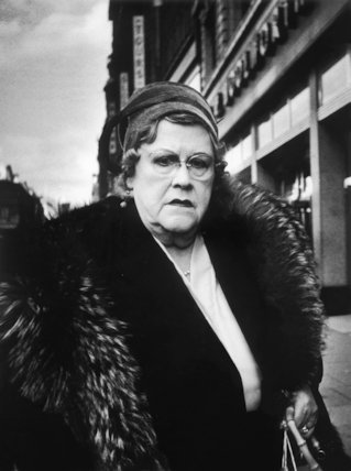 A woman in a fur coat outside a London branch of Woolworths: 1961