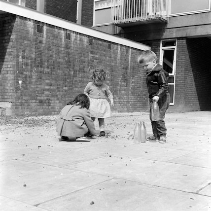 Children playing with milk bottles and stones,c1960.