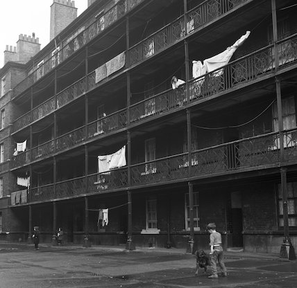 Boy and dog outside block of flats. c.1955