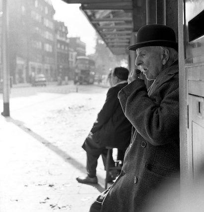 Man in bowler hat siting beneath roof or awning. c.1955