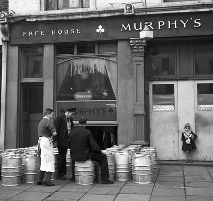 Three men outside a pub with a delivery of beer kegs. c.1955