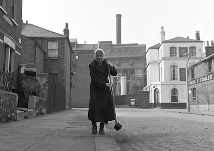 Woman standing on pavement holding a broom. c.1955